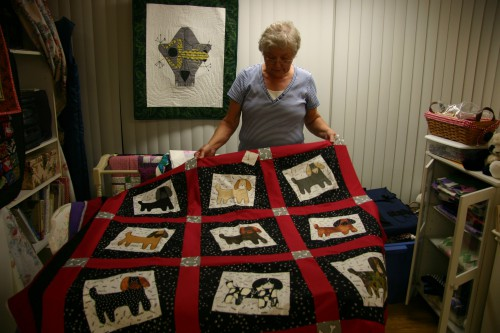 Sandra displays a quilt of dog images; behind her on the wall is a Charley Harper quilt.