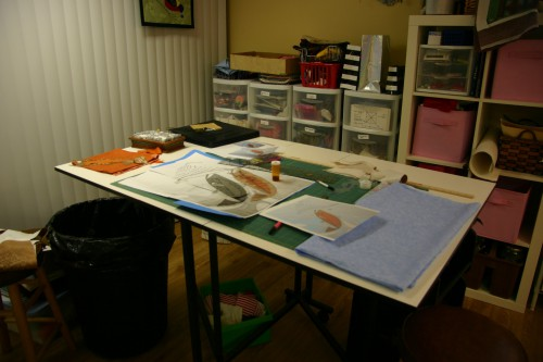 Sandra's worktable, where she is working on a Charley Harper quilt with a fish the central figure.