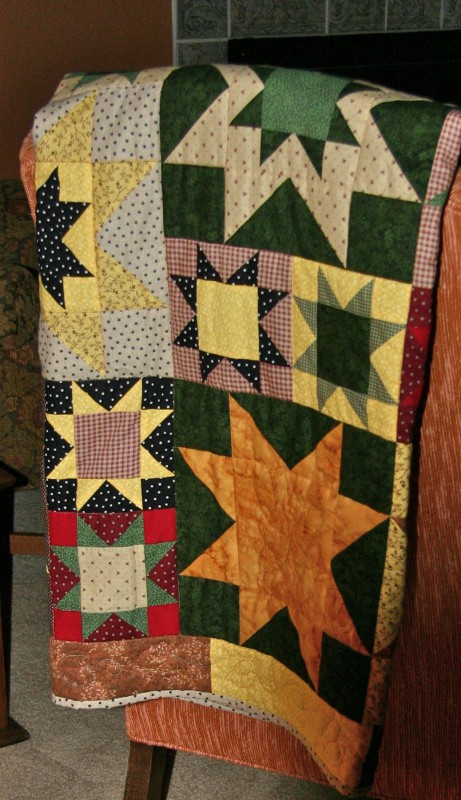 Sandra's quilt, on a chair in the front room, in which she worked the star block pattern with variations of size and  fabric illustrating the graphic power of the quilt.