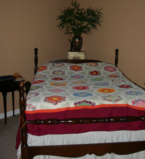A guest bed welcomes visitors with Rosa Smiley's quilt pieced with hexagons in the pattern Grandmother's Flower Garden.