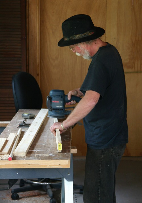 Michael steps in to help with the sanding, rounding edges just enough to make the easel a pleasure to handle.